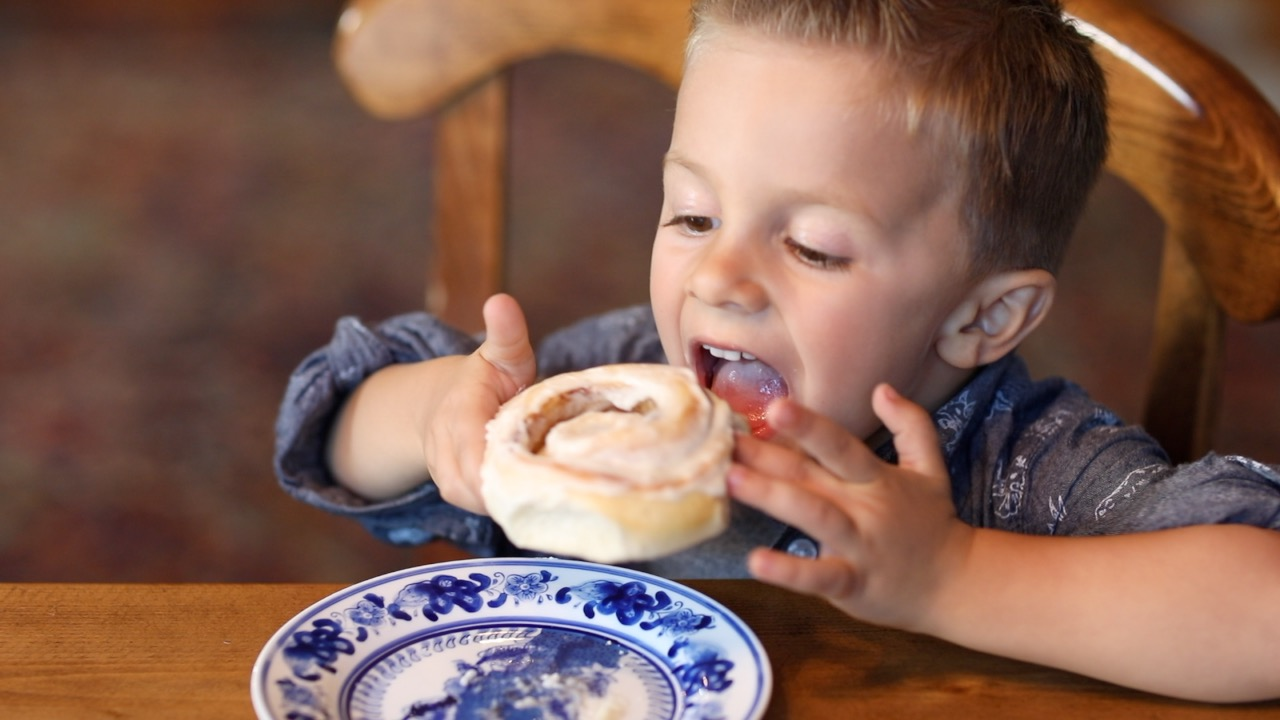 Boy Eating Cinnamon Roll
