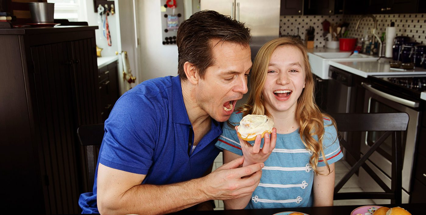 Father and daughter eating Rhodes Cinnamon Rolls