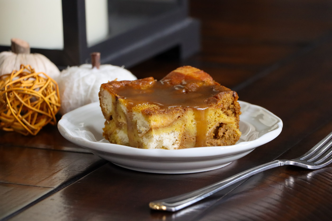 A piece of pumpkin bread pudding with brown sugar sauce over the top.